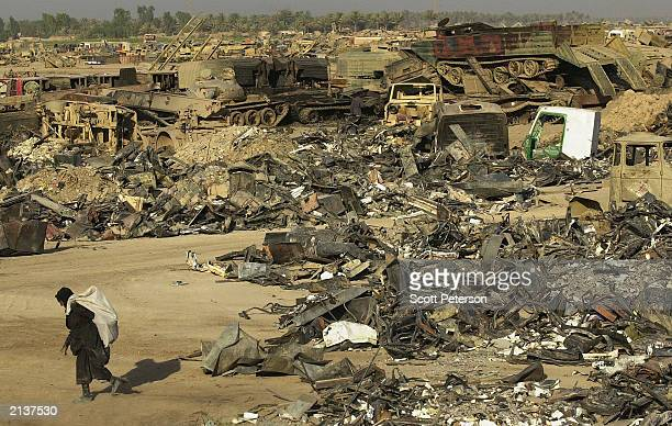 """An Iraqi scrap dealer takes their haul away after scavenging the """"tank graveyard"""" of Iraqi military hardware and vehicles created by U.S. Troops June..."""