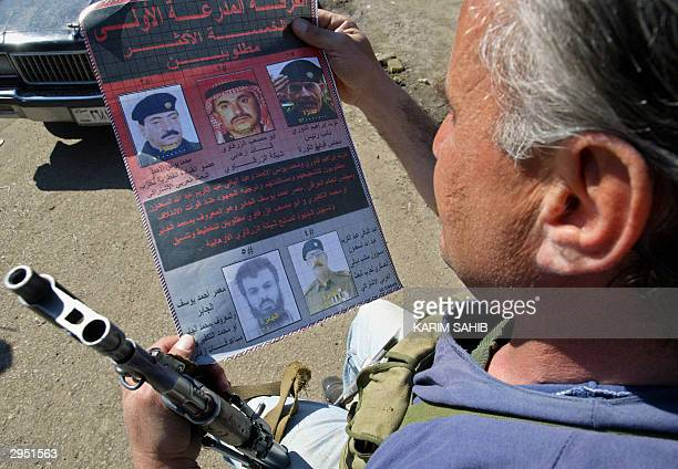 An Iraqi security man looks at a new poster distributed by the US army offering a total of 165 million dollars for the capture of the five most...
