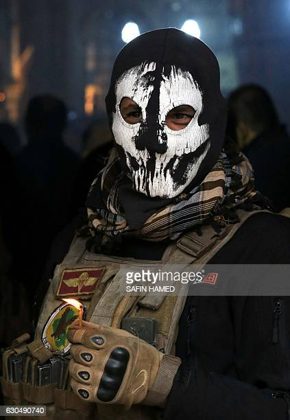 CORRECTION An Iraqi security member attends a Christmas Eve service at the Mar Shimoni church in the town of Bartalla near Mosul on December 24 for...