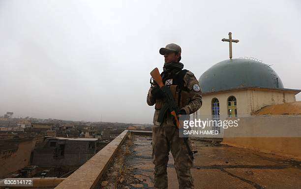 An Iraqi security member stands guard as Iraqi Christians attend a Christmas Eve service at the Saint John's church in the town of Qaraqosh 30 kms...