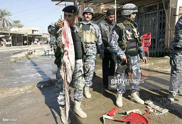 An Iraqi security officer holds up a bloodied piece of garment as he and others stand in front of a shattered plastic chair following an explosion at...