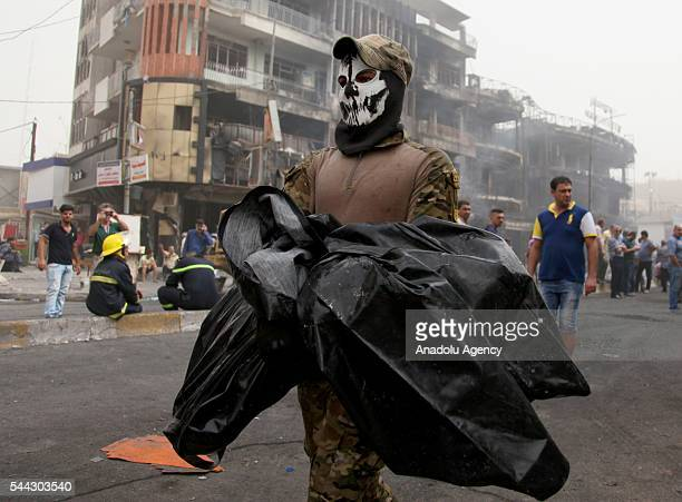 An Iraqi security personnel carries a dead body of a citizen after a suicide car bombing claimed by the terrorist organization DAESH in the Karrada...