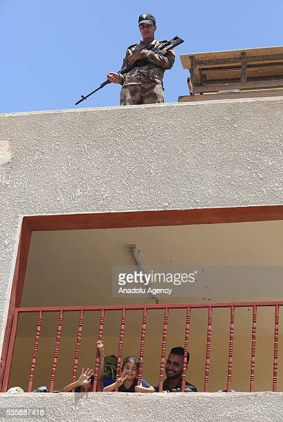 An Iraqi security soldier stands guard on the roof as Iraqi people in Fallujah town leave their home due to conflicts between Daesh and security...