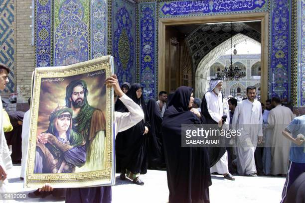 An Iraqi sells posters of Imam Ali cousin of Islam's Prophet Mohammed during the Friday prayer at Imam Ali's shrine in the holy city of Najaf 180...