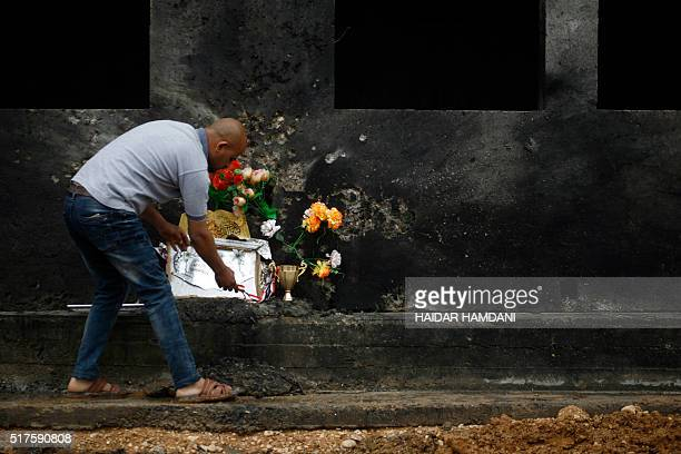 An Iraqi sets up a makeshift memorial on March 26 2016 at the site where a suicide bomber blew himself up the day before in a village near...
