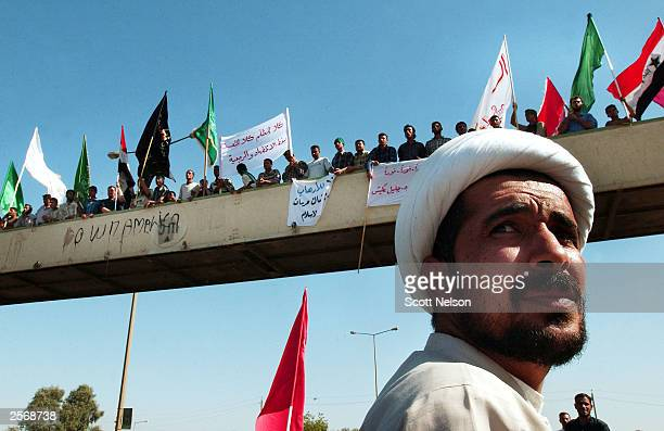 An Iraqi Shia cleric keeps a watchful eye on US soldiers gathering nearby during a protest against the detention of local Shia Imam Mo'ayed...