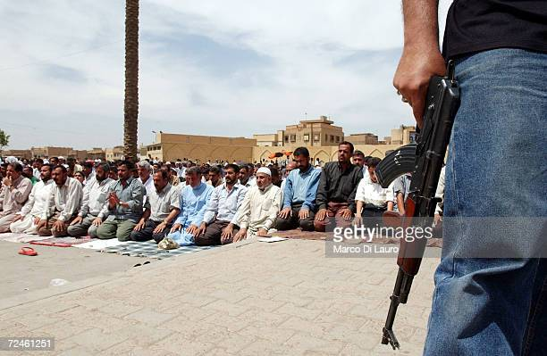 An Iraqi Shia holds a rifle as thousands of Muslim Shias gathering for the Friday prayer in front of the Kadhimain Mosque May 2 2003 in Baghdad Iraq...