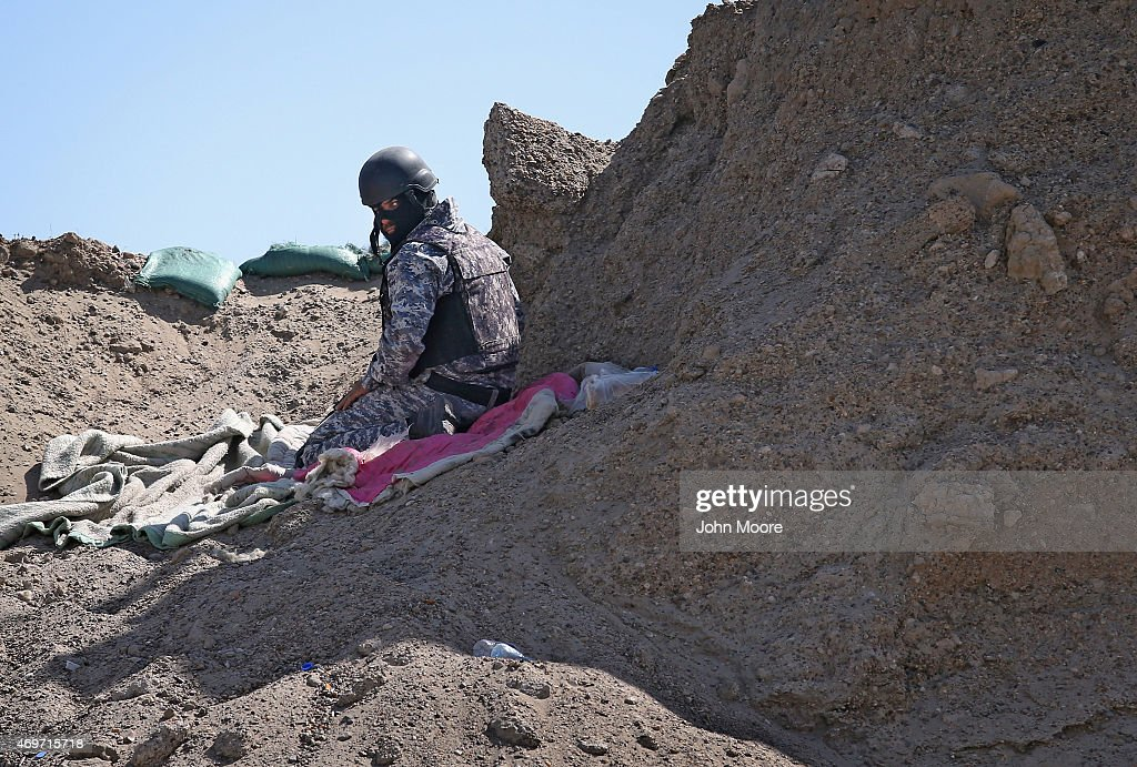 An Iraqi Shia militia fighter sits in an overwatch position as Iraqi government troops assault ISIL fighters on the frontline on April 14, 2015 near Al-Karmah, in Anbar Province, Iraq. Iraqi government forces are assaulting ISIL fighters on frontline positions which were established last year when ISIL captured much of the province.