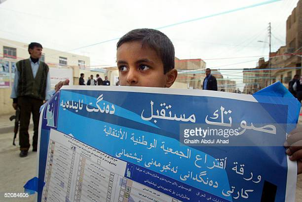 An Iraqi Shiite boy holds an election poster January 30 2005 in the Shiite holy city of Najaf Iraq Najaf enjoyed a calm election day with no violence...