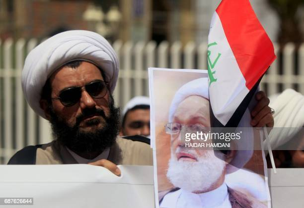 An Iraqi Shiite cleric holds a picture of top Bahraini Shiite cleric Isa Qassim during a demonstration in front of the Bahraini consulate in Najaf on...