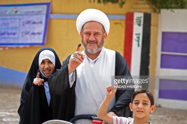 An Iraqi Shiite cleric shows his inkstained index finger and children imitate him outside a polling station in the central holy city of Najaf on May...