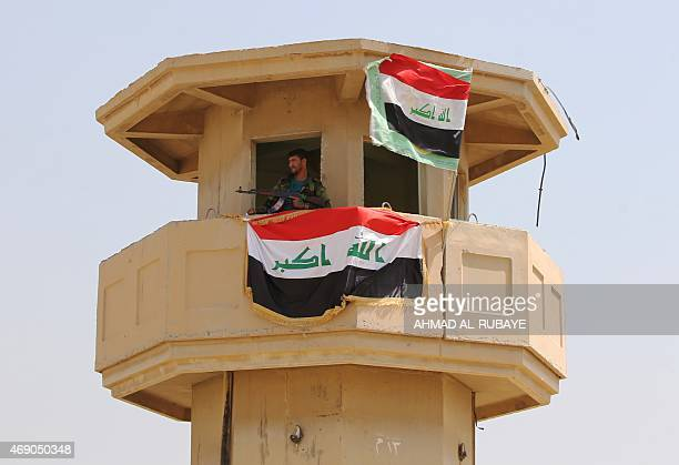 An Iraqi Shiite fighter and member of Iraq's Popular Mobilisation Unit stands inside a watchtower on April 9 2015 located in the area of former Iraqi...