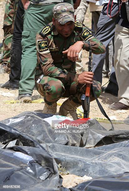 An Iraqi Shiite fighter and member of Iraq's Popular Mobilisation Unit mourns over bodybags containing the remains of people believed to have been...