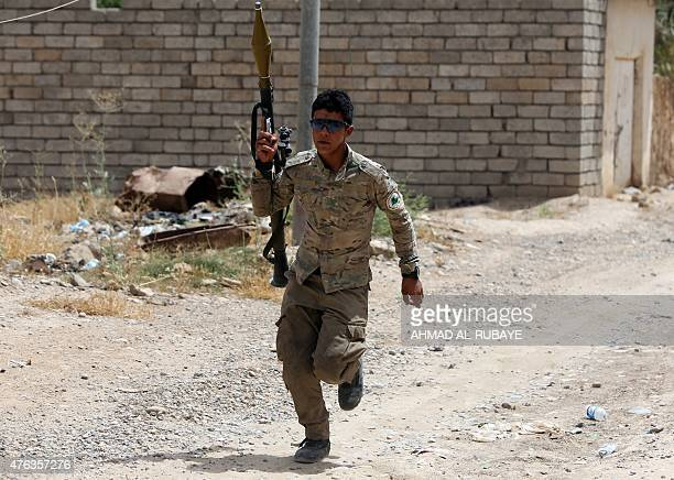 An Iraqi Shiite fighter from the Popular Mobilisation force runs with a rocketpropelled grenade during a battle against jihadists from the Islamic...