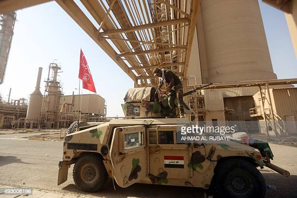 An Iraqi Shiite fighter from the Popular Mobilisation units fighting alongside Iraqi forces cleans his weapon on his vehicle at the petrochemical...