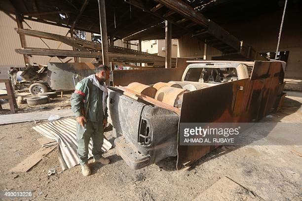 An Iraqi Shiite fighter from the Popular Mobilisation units fighting alongside Iraqi forces inspects a pickup truck which was prepared for a bomb...