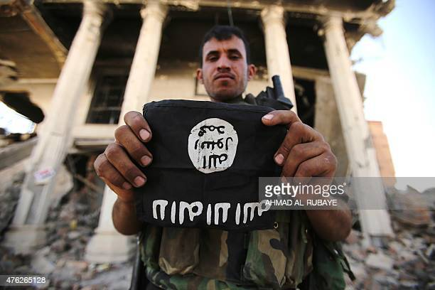 An Iraqi Shiite fighter from the Popular Mobilization units holds an Islamic State group patch as he inspects a council building in the city of...