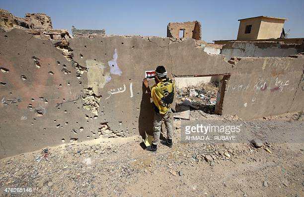 An Iraqi Shiite fighter from the Popular Mobilization units places an Iraqi flag sticker on a wall in the city of Baiji north of Tikrit in the...
