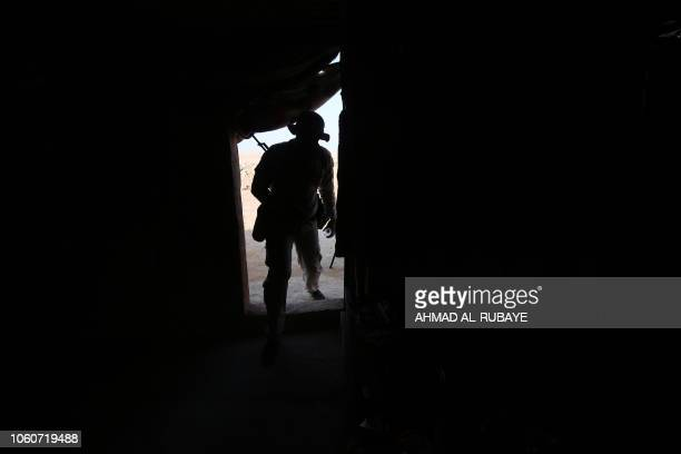 An Iraqi Shiite fighter of the Hashed alShaabi paramilitary force enters a tent as he secures the border in alQaim in the Anbar province opposite...