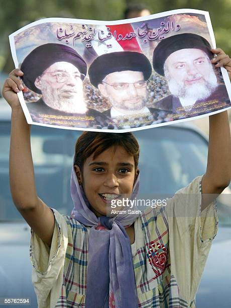 An Iraqi Shiite girl carries a picture of Shiite clerics as she takes part in a march to support of Iraq's new constitution on September 24 2005 in...