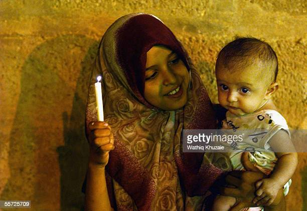 An Iraqi Shiite girl holds a candle and child September 19 2005 in the city of Karbala 70 miles south of Baghdad Iraq Hundreds of thousands of Iraqi...