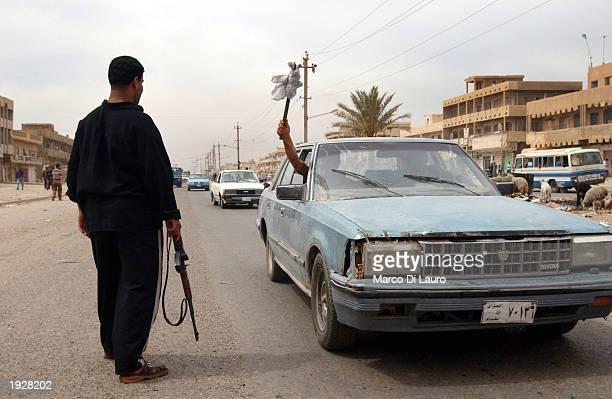 An Iraqi Shiite gunman searches a car at a check point in the Shiite neighborhood of Saddam City April 13 2003 in Baghdad Iraq Widespread looting...