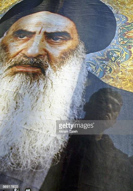 An Iraqi Shiite man carries a picture of Iraq's powerful Shiite cleric Grand Ayatollah Ali al-Sistani as he takes part in a protest against the...