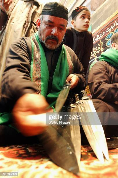 An Iraqi Shiite man cleans his sword as he prepares to flagellate himself in honor of Imam Hussein's death anniversary on February 8 2006 in the city...