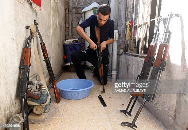 An Iraqi Shiite man cleans weapons as he gets ready to defend his Sadr City district in case of an attack by Sunni extremists, on June 13, 2014 in...
