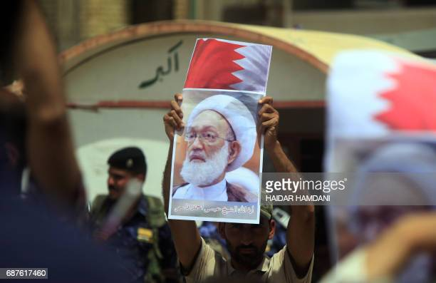 An Iraqi Shiite man holds a picture of top Bahraini Shiite cleric Isa Qassim during a demonstration in front of the Bahraini consulate in Najaf on...