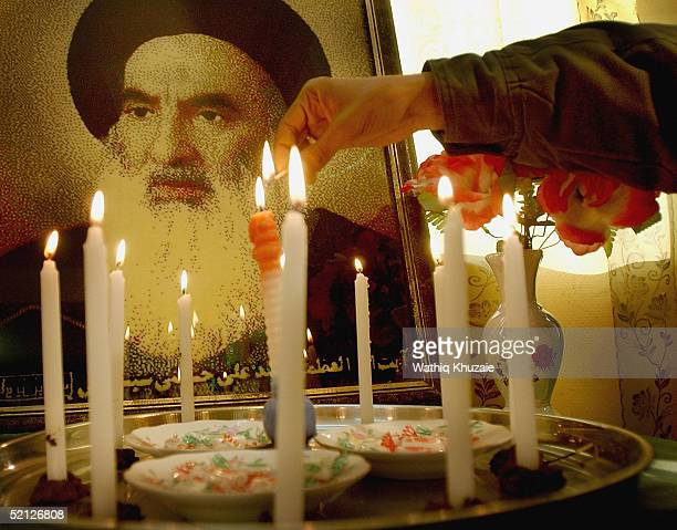An Iraqi Shiite man lights candles near a picture of the Shiite cleric Ayatollah Ali al-Sistani as he celebrates a successful end to the elections on...