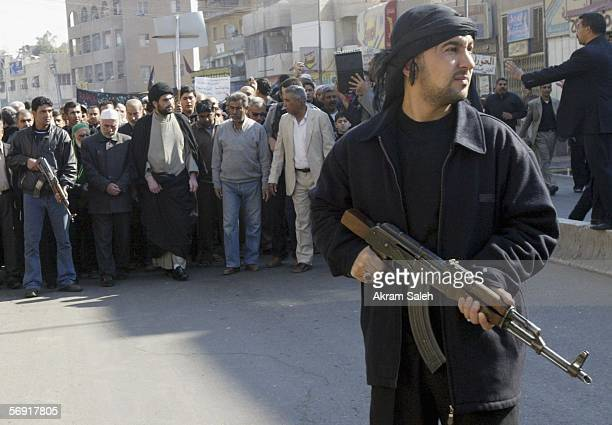 An Iraqi Shiite man provides security as others take part in a protest against the bombing of a Shiite holy shrine on February 23 2006 in the...