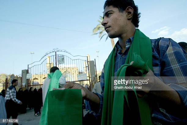 An Iraqi Shiite man sells green cloth used for blessings at the gates of the Kadhmiya Shrine November 14 2004 in Baghdad Iraq The Kadimya Shrine is...