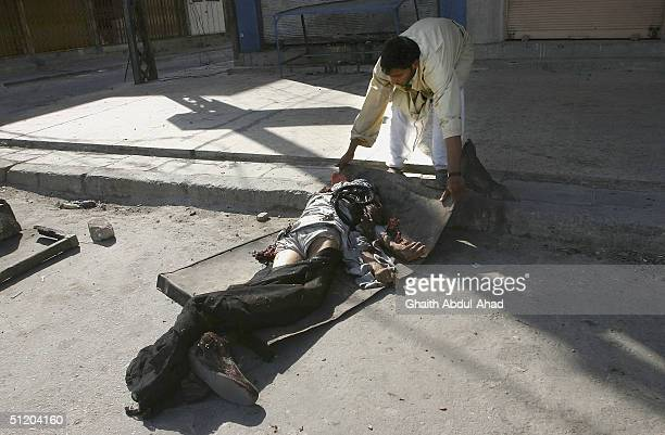 An Iraqi Shiite militia man drags a dead civilian from Madina street close to the shrine of Imam Ali on August 22 2004 in Najaf Iraq After a night of...