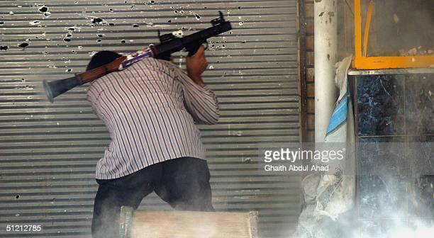 An Iraqi Shiite militia man runs to take cover after firing his RPG launcher at U.S tank on the eastern front lines of the old town on August 24,...