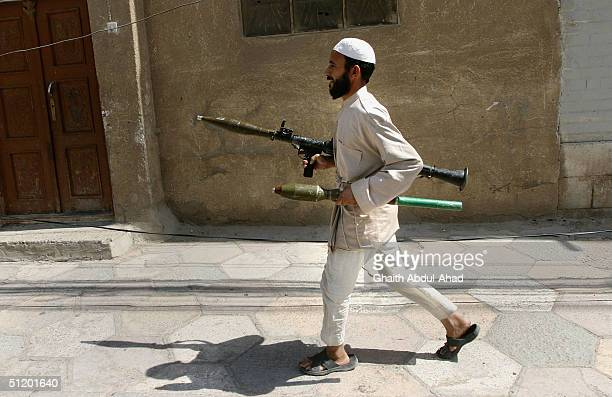 An Iraqi Shiite militia man runs towards advancing US tanks with an RPG launcher August 21 2004 in Najaf Iraq The militia loyal to the radical Shiite...