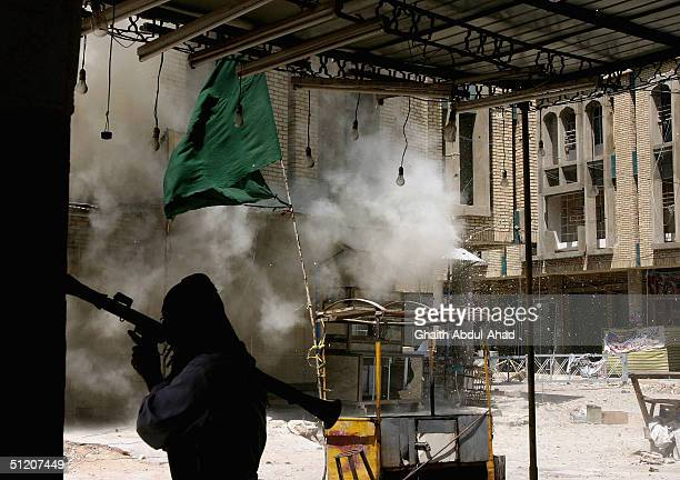 An Iraqi Shiite militia man takes cover as shells hit a building from where Mahdi fighters were shooting at US forces August 23 2004 in Najaf Iraq