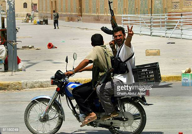 An Iraqi Shiite militiaman flashes a victory sign as he rides on the back of a motorcycle toward clashes with US Marines August 7 2004 in Najaf Iraq...