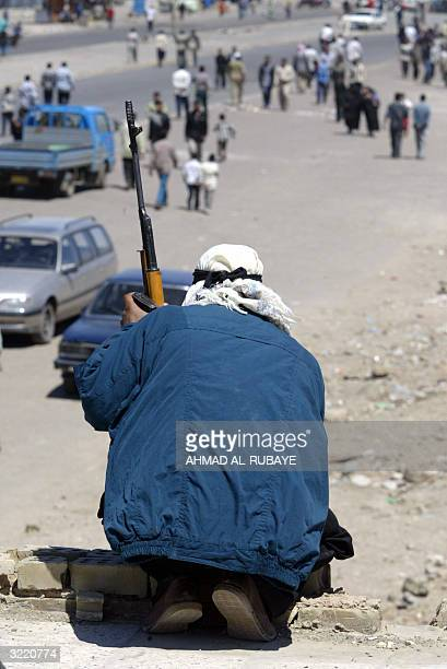An Iraqi Shiite Muslim gunman member of Shiite radical leader Moqtada alSadr Army of Mehdi militia takes position on a rooftop in Baghdad's Shiite...