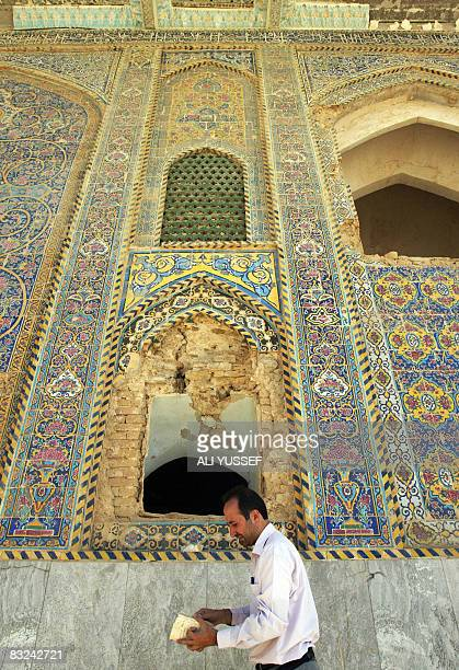 An Iraqi Shiite Muslim reads a book as he walks past the AlAskari mosque in Samarra on October 4 2008 This sacred Shiite site was baddly damaged when...
