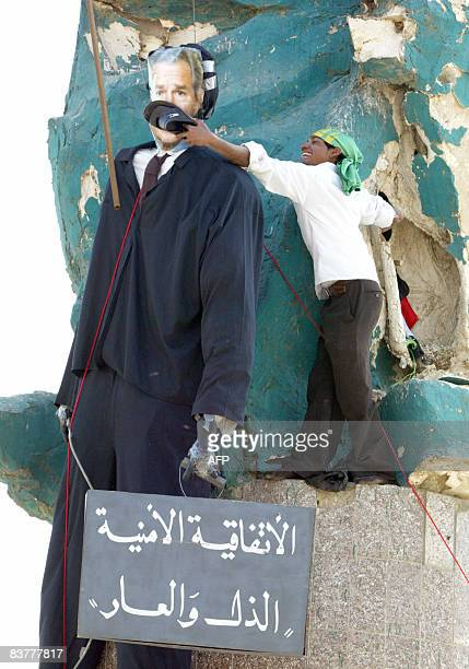 An Iraqi Shiite Muslim uses a slipper to hit the face of an effigy of US President George W Bush and a sign that reads in Arabic 'The security...