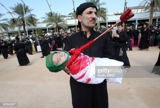 An Iraqi Shiite Muslim worshiper holds a baby dressed up to represent Abdullah referred to as Ali alAsghar the son of the Prophet Mohammed's grandson...