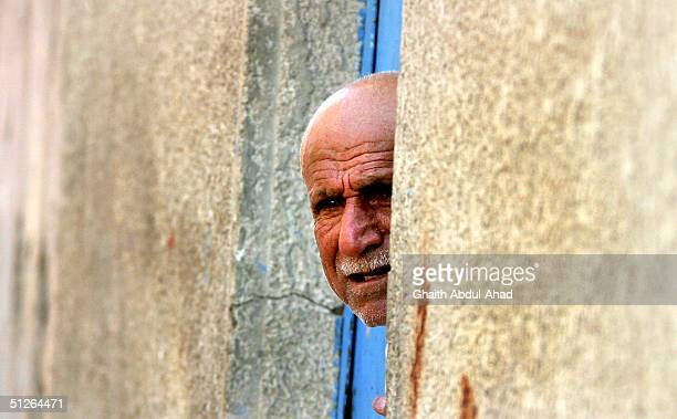 An Iraqi Shiite old man put his head out of his door after hearing explosions during fighting in the Shiite area of Sadr city east of Baghdad on...