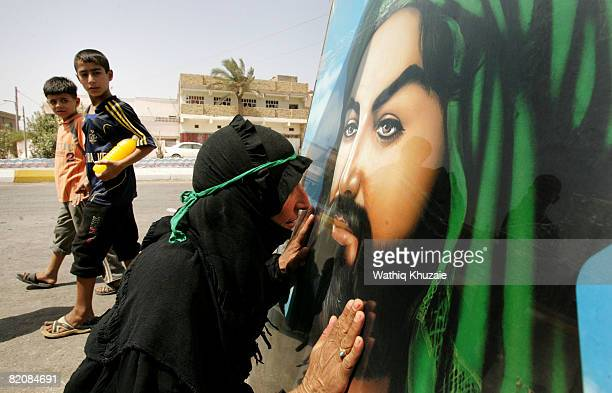 An Iraqi Shiite pilgrim kisses a picture of Shiite Imam Hussein as she marches towards the Shrine of Shiite Imam Musa alKadhim on July 28 2008 in...