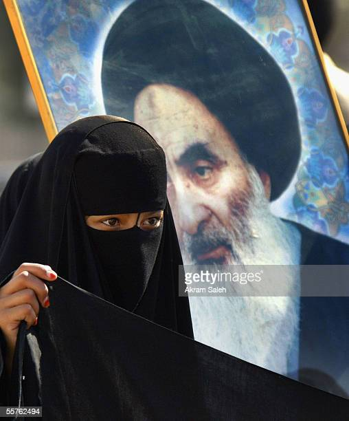 An Iraqi Shiite woman participates in a demostraion to support Iraq's new constitution in front of a of picture of Shiite cleric Ayatollah al-Sistani...
