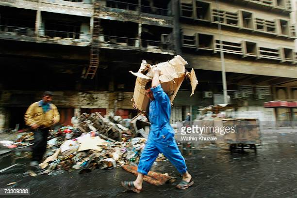 An Iraqi shopkeeper carry goods at the site of yesterday's car bomb explosion on February 13 2007 at Shorja market in Baghdad Iraq A car bomb...