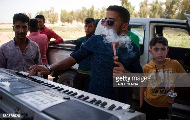 An Iraqi smokes a waterpipe as he plays an electronic keyboard for others as they dance in a park in the Shallalat district northeast of the...