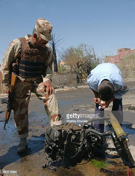 An Iraqi soldier and policeman investigate the scene of a car bomb explosion September 8, 2005 in central Baghdad, Iraq. The blast targeted a passing...