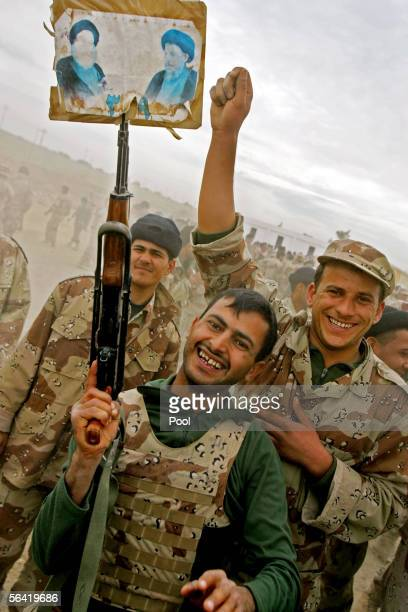 An Iraqi soldier displays a placard with images of prominent Shiite clerics Grand Ayatollah Ali al-Sistani and Mohammad Baqir al-Sadr on his rifle as...