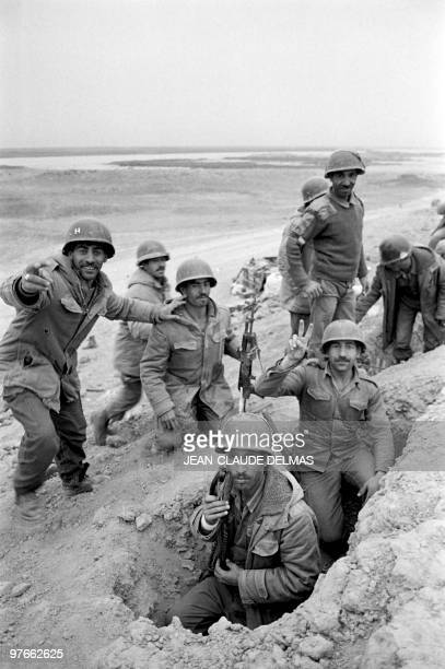 An Iraqi soldier flashes a Vsign as his comrades look on in a trench dug near AlHoweizah swamps north of Basra on March 18 1985 The IraqIran war...